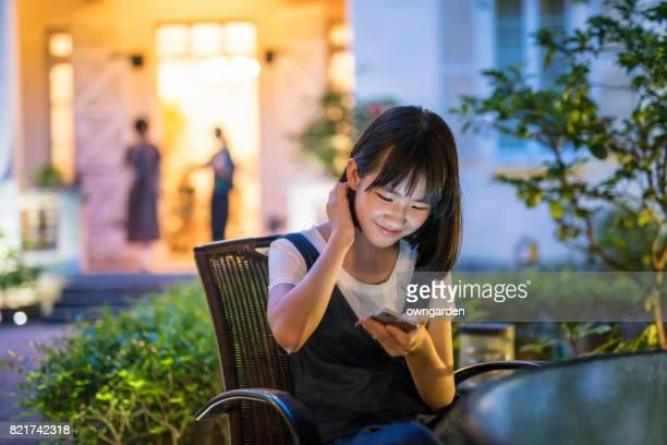 Teenage girl using smartphone in the garden