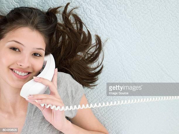 A teenage girl using the telephone
