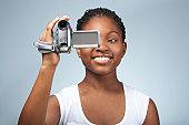 Teenage girl (15-17) using video camera, smiling, close-up
