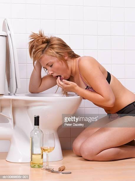 Teenage girl (16-17) vomiting into toilet bowl