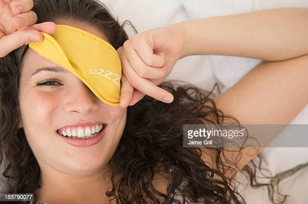 Teenage girl waking up, peeking out of sleep mask