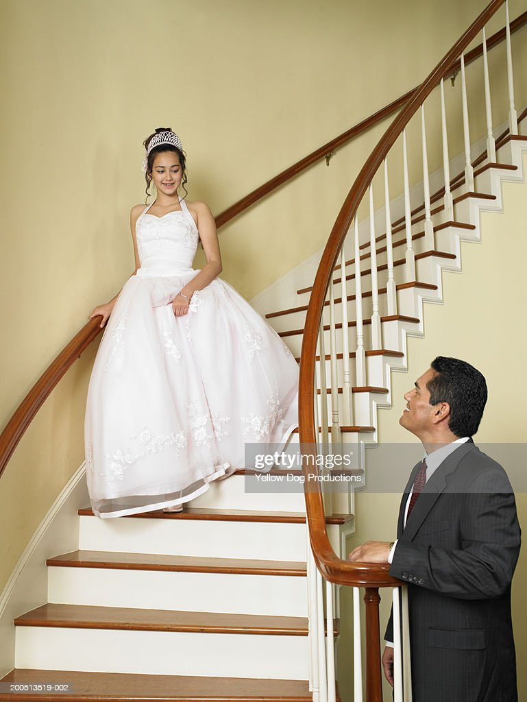 Teenage girl (14-16) walking down stairway to father, wearing dress : Stock Photo
