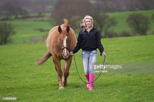 Teenage girl walking horse in field