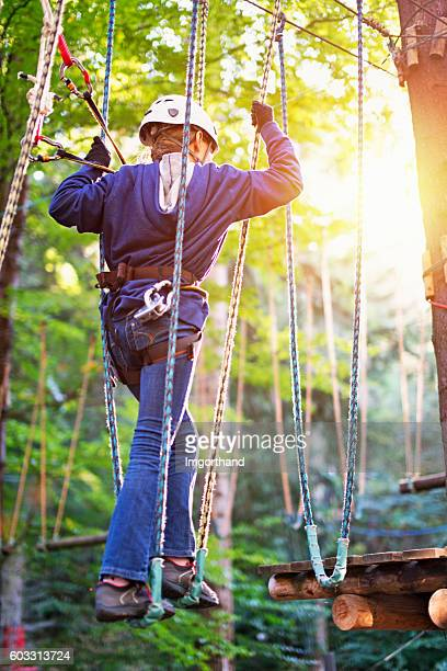 Teenage girl walking in ropes course adventure park