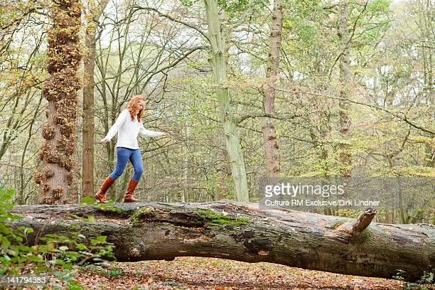 Teenage girl walking on log in forest