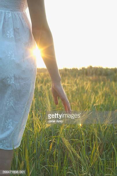 Teenager Mädchen (26) zu Fuß durch lange Gras, Nahaufnahme