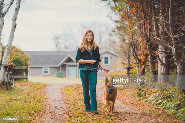 Teenage girl walking with shepherd dog on a beautiful autumn day