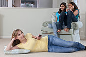 Teenage girl watching television with her Hispanic friends listening to an MP3 player