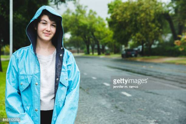 Teenage girl wearing a blue raincoat during a rain event in Austin, Texas