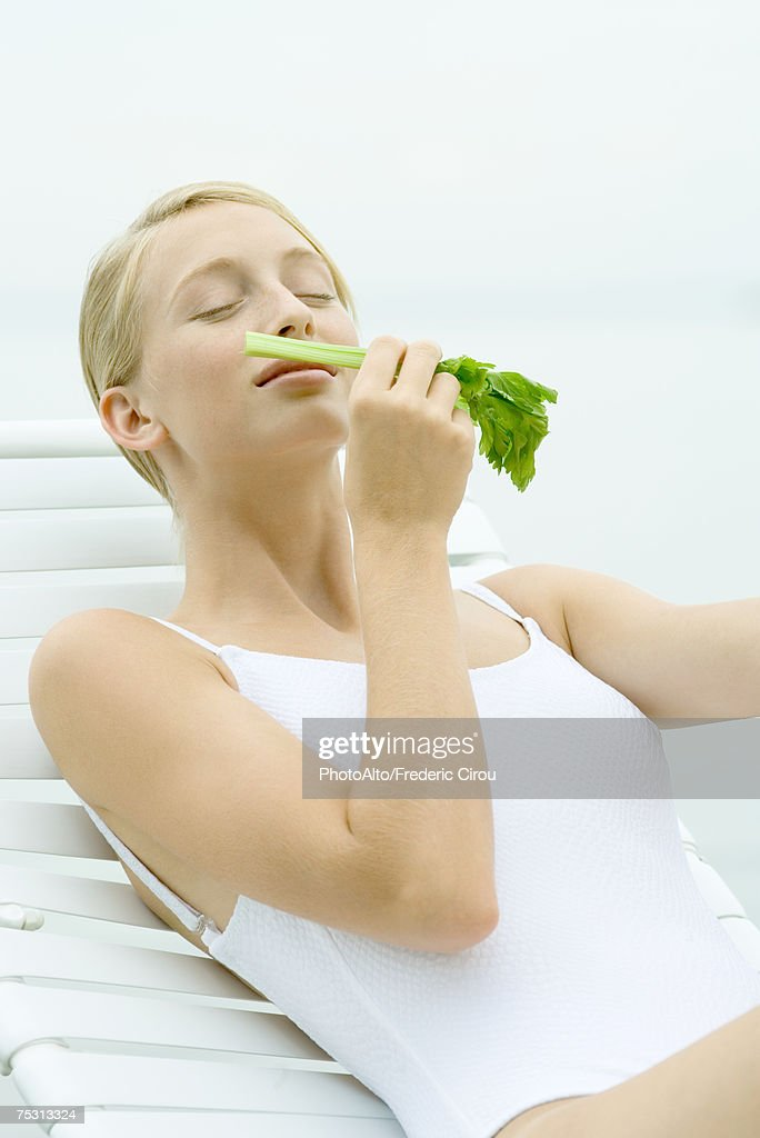 Teenage girl wearing bathing suit, sitting in lounge chair, smelling celery stalk : Stock Photo