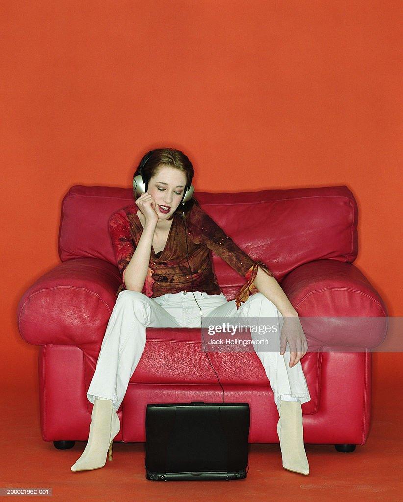 Teenage girl (16-18) wearing headphones, using laptop : Stock Photo