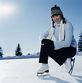 Teenage girl (14-16) wearing ice skates, crouching on ice, portrait