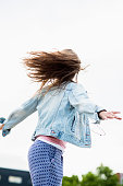 Teenage girl wearing jeans jacket jumping into the air, back view