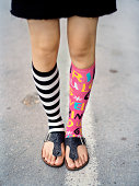Teenage girl wearing mismatched socks, low section