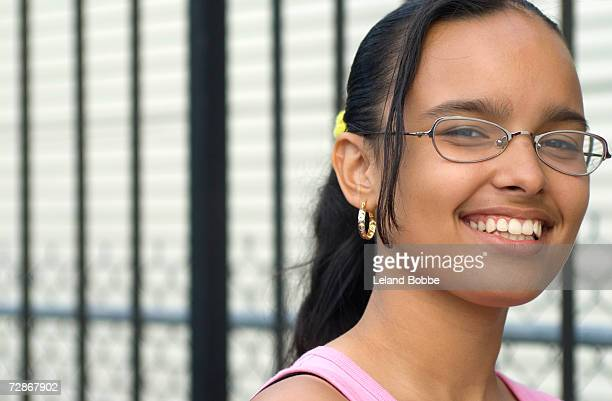 Teenage girl (14-15) wearing spectacles, smiling, portrait