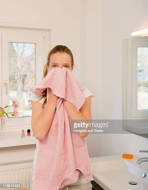 Teenage girl wiping her face with towel