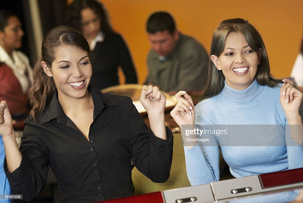 Teenage girl with a young woman playing on slot machines : Foto de stock