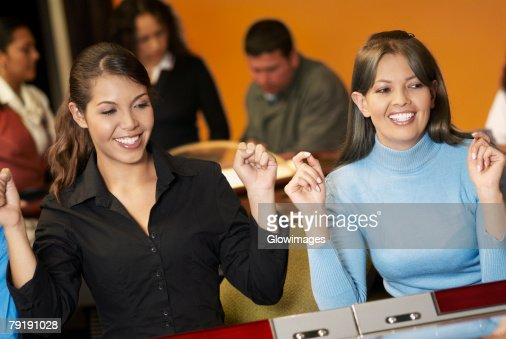 Teenage girl with a young woman playing on slot machines : Stock Photo