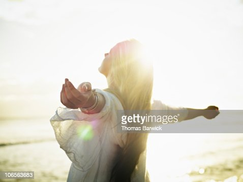 Teenage girl with arms outstretched at sunset : Stock Photo