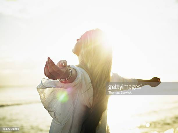 Teenage girl with arms outstretched at sunset