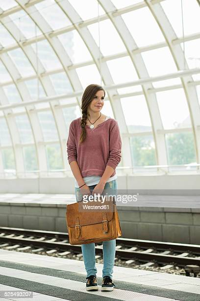 Teenage girl with bag at commuter train station