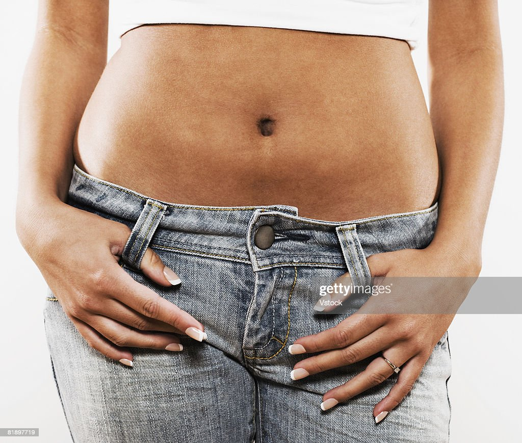 Teenage girl with bare midsection and thumbs in belt loops