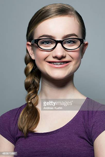 Teenage girl with braces and glasses, smiling.