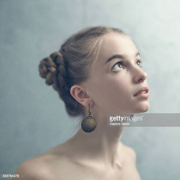 Teenage girl with braided hair wearing dangling earrings