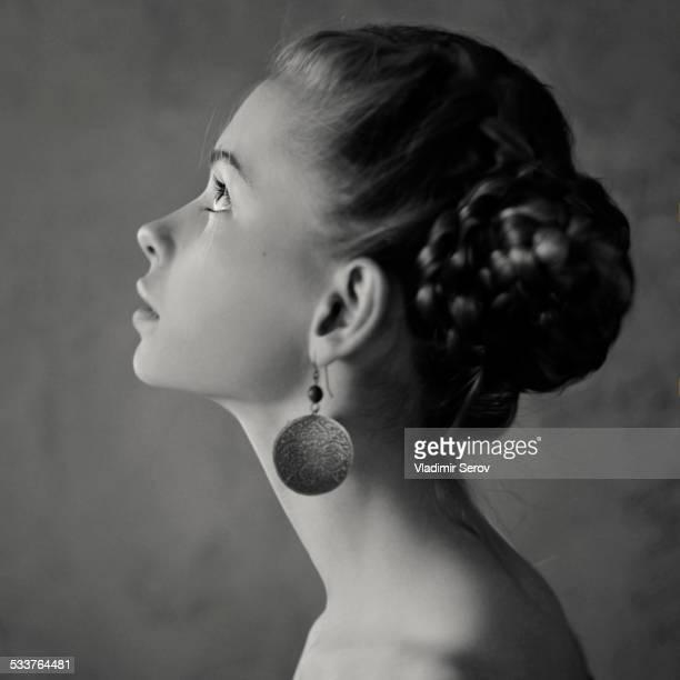 Teenage girl with braided hair wearing dangling earrings