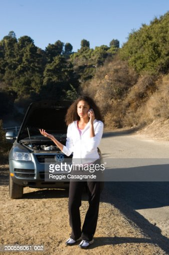 Teenage girl (16-17) with broken down car by road, using mobile phone : Stock Photo
