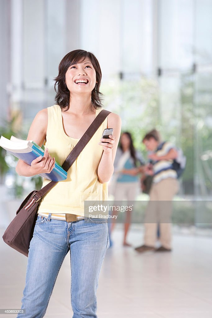Teenage girl with cell phone and books at school