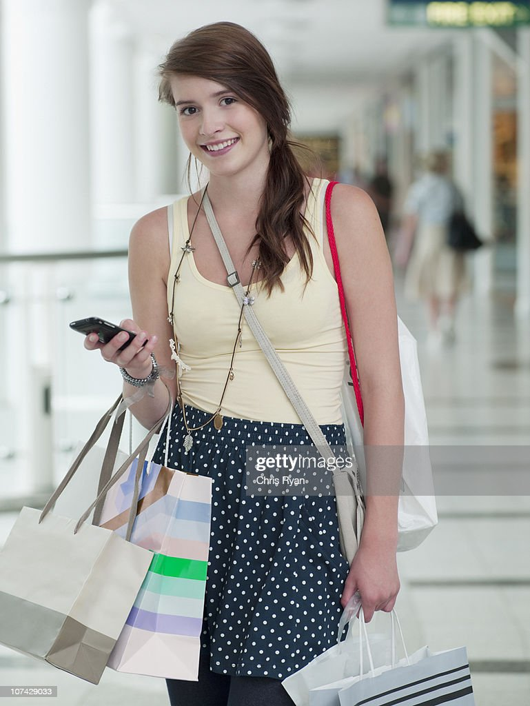 Teenage girl with cell phone carrying shopping bags in mall : Stock Photo
