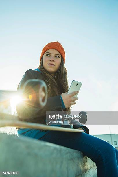 Teenage girl with cell phone in skatepark