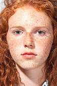 Teenage girl (13-15) with curly hair and freckles, close-up, portrait