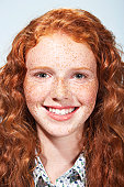 Teenage girl (13-15) with curly hair and freckles, smiling, portrait
