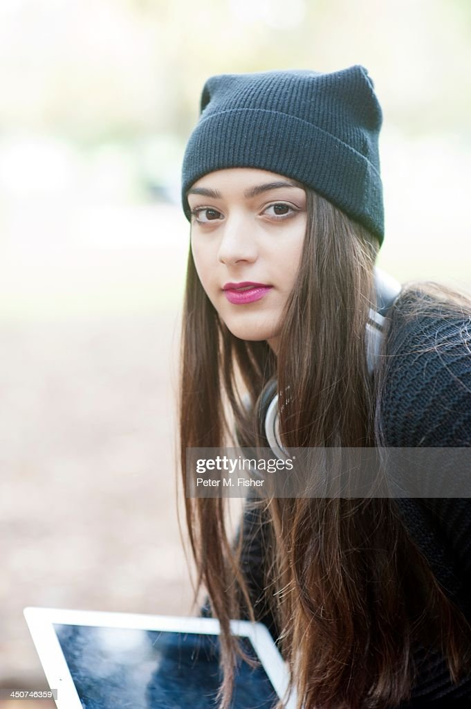 Teenage girl (16-17) with digital tablet and woolen hat
