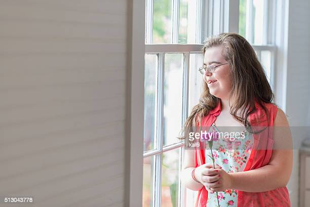 Teenage girl with down syndrome looking out window