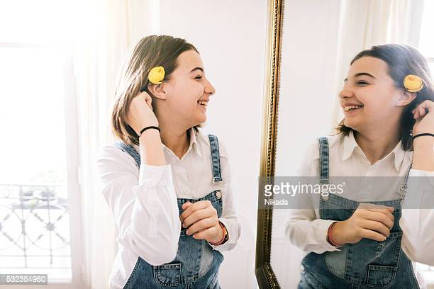 Teenager-Mädchen mit Blume Blick in den Spiegel