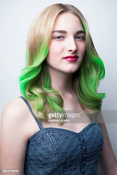 Teenage girl with green color in her hair.