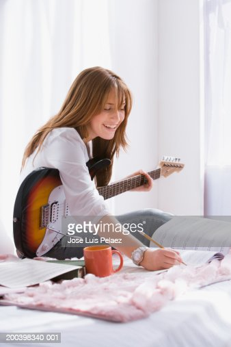 Teenage girl (14-16) with guitar writing in music book on bed, smiling : Photo