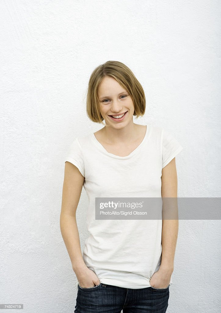 Teenage girl with hands in pockets, front view