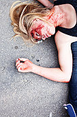 Young woman with laying on the ground on top of another (unrecogniszable) person with blood on her face after an accident