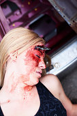 Young woman with laying on the ground with blood on her face after an accident