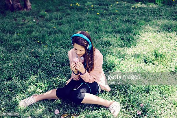 Teenage girl with headphones in the grass