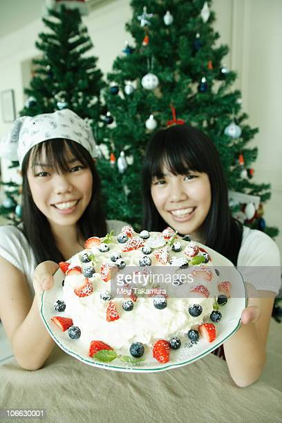 Teenage girl with her sister holding a fruit cake and smiling
