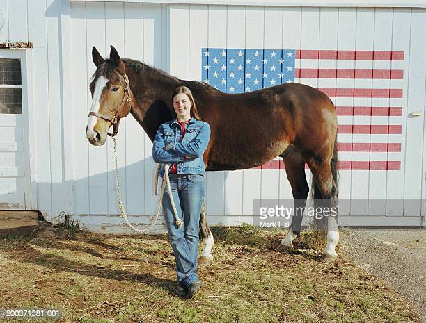 Teenage girl (17-19) with horse smiling, portrait