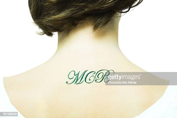 'Teenage girl with initial's tattooed onto upper back, close-up'