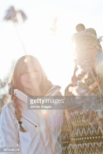 Teenage girl with mother looking through frosted grass : Stock Photo