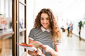 Attractive teenage girl with notebooks in high school hall during break.