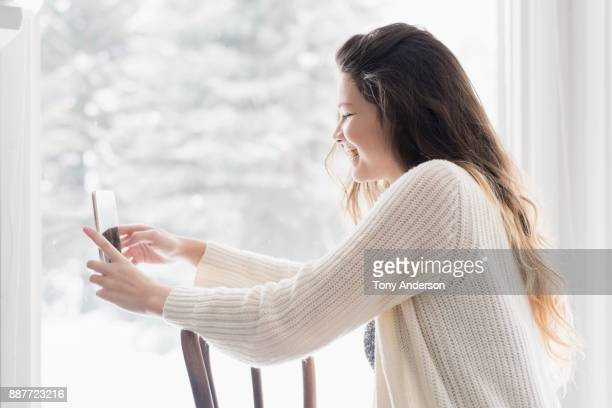 Teenage girl with phone sitting on chair indoors